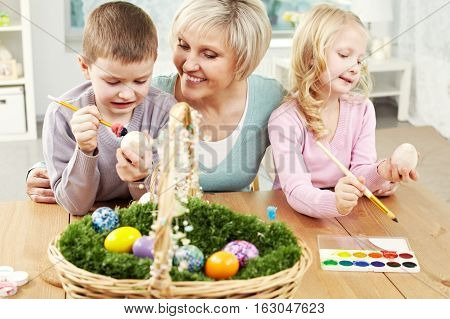 Little children coloring Easter eggs for Christmas with their granny