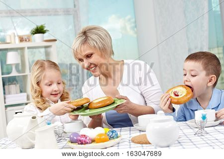 Grandma treating her little grandchildren with buns