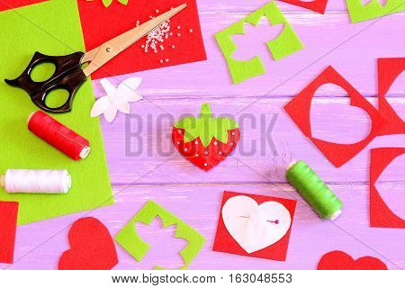 Sewing toy, tools and materials. Felt strawberry toy, scissors, red and green felt sheets and scraps, thread, needle, paper pattern, beads on lilac wooden background. Craft background. Top view