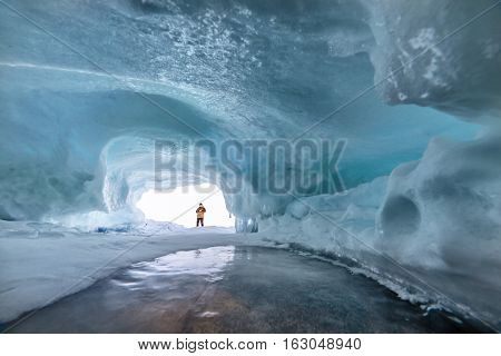 Ice cave on Lake Baikal in winter. Small silhouette of man in it.