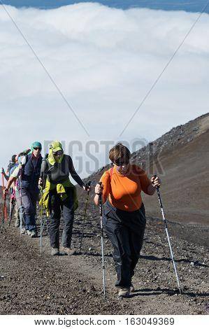 AVACHINSKY VOLCANO KAMCHATKA RUSSIA - AUGUST 7 2014: Hiking on Kamchatka - group of women travelers and tourists climbing on tourist trail to top of Avacha Volcano on Kamchatka Peninsula.
