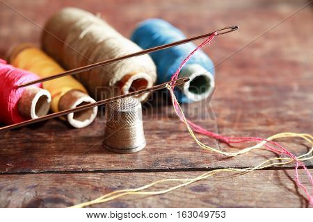 Thimble and needles near thread on old wooden background