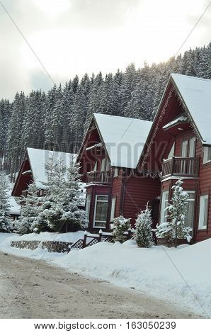 view of scenic white winter landscape in the Alps with traditional mountain chalet