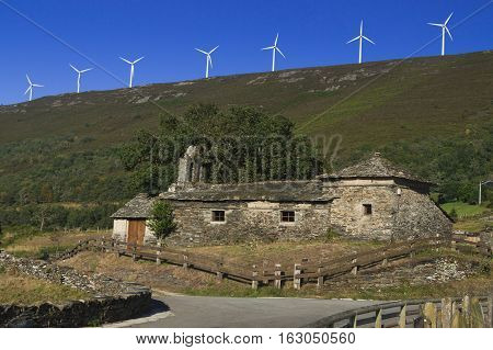 Spain Asturias ancient church in the foreground wind turbines in the background ancient and modern juxtaposition