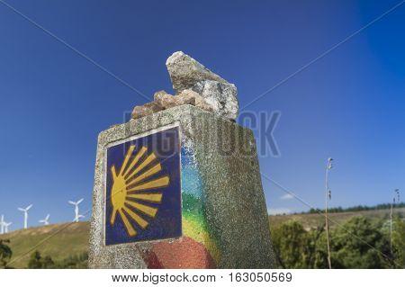 Spain Galicia rainbow painted milestone at the Camino de Santiago camino Primitivo; wind turbines in the background