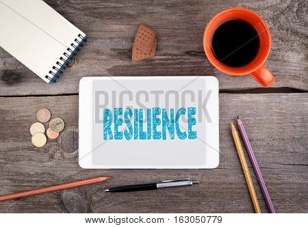 Resilience. Text on tablet device on a wooden table