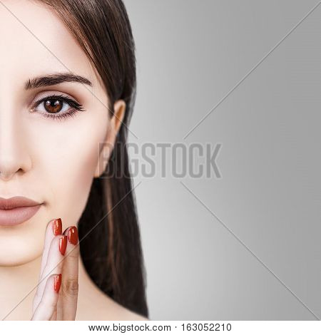 Half-face portrait of beautiful sensitive woman over gray background