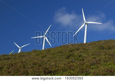 Spain Asturias wind turbines on a hill clouds