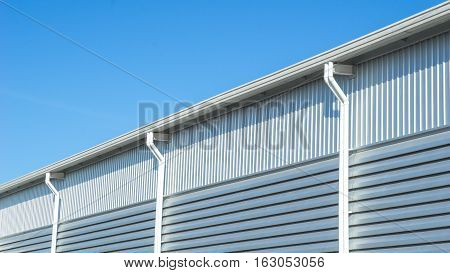 Factory warehouse and industrial concept - Close up wall and roof of Factory or warehouse building in industrial estate with blue sky and copyspace poster