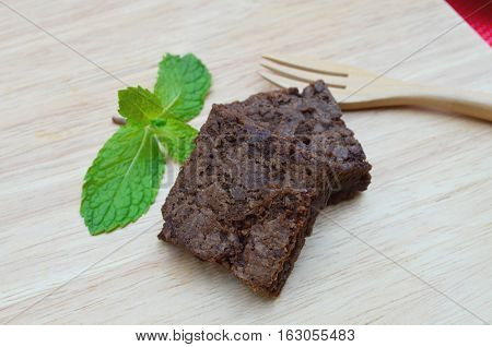 Delicious and soft fresh homemade brownie chocolate square and sliced decorate with peppermint on wooden board