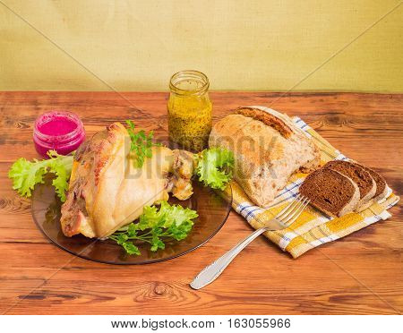 Baked ham hock with lettuce and parsley on a glass dish beet horseradish sauce French mustard in small glass jars fork and different bread on a napkin on a surface of old wooden planks
