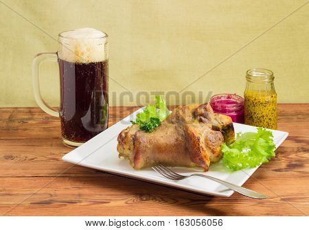 Baked ham hock with lettuce and parsley on a square white glass of dark beer condiment and fork on a surface of old wooden planks