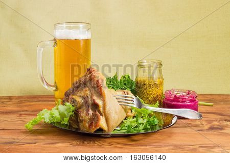 Baked ham hock with lettuce and parsley on a glass dish glass of lager beer beet horseradish sauce French mustard fork on an old wooden surface
