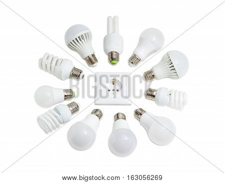Several different domestic light emitting diode lamps and compact fluorescent lamps with a sized E27 male screw base around the power socket on a light background poster