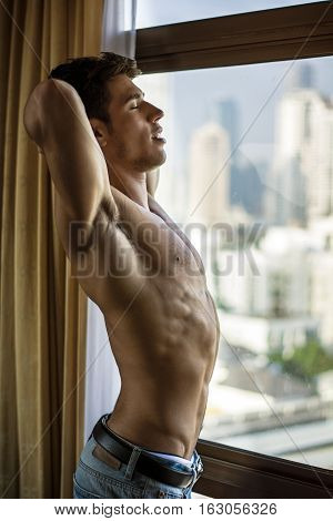 Young shirtless man stretching with eyes closed near window. Vertical indoors shot