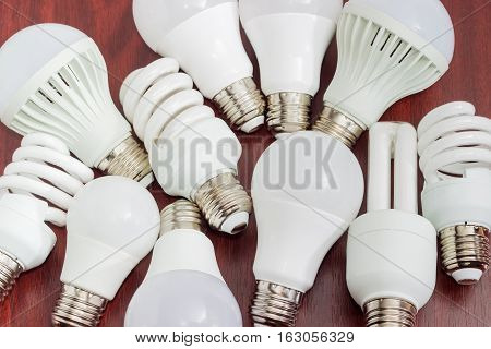 Several different domestic light emitting diode lamps and compact fluorescent lamps with a sized E27 male screw base closeup on a dark wooden surface