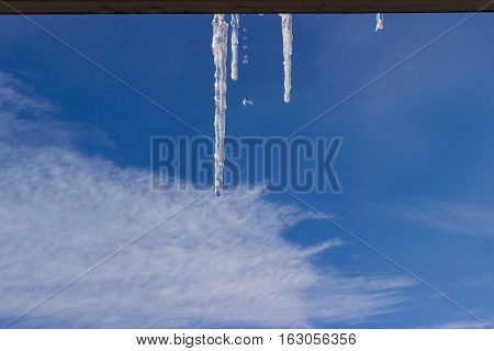Several icicles with falling water drops on cornice of window on background of the sky with cirrus clouds