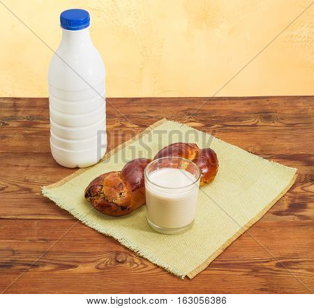 Plastic bottle and glass of fermented baked milk and baked braided pie with filling made of finely ground poppy seeds on an old wooden surface