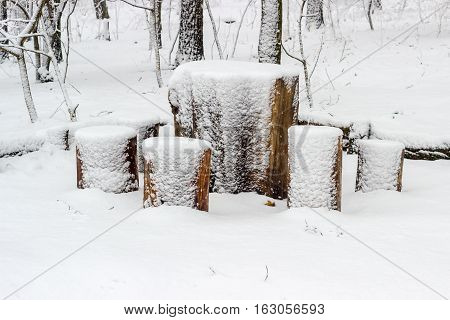 Table and chairs made from old stump and wooden logs covered fluffy snow