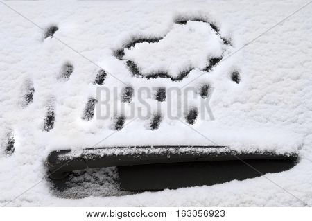Car window and wiper covered with snow and drawn snowfall closeup cropped shot