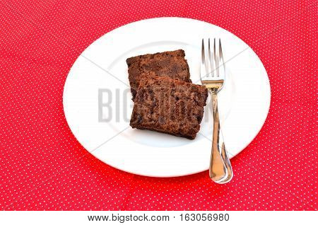 Delicious and soft fresh homemade brownie chocolate square and sliced on white dish