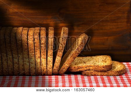 Row of healthy rusks of wholemeal flour on a table with red and white checkered tablecloth and wooden dark wall