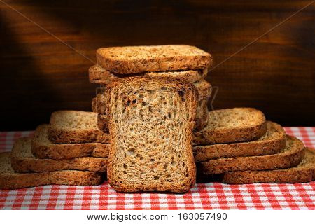 Group of healthy rusks of wholemeal flour on a table with red and white checkered tablecloth and wooden dark wall