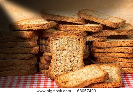 Group of healthy rusks of wholemeal flour on a table with red and white checkered tablecloth and wooden wall