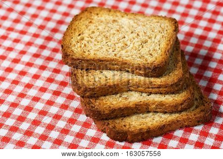 Four healthy rusks of wholemeal flour on a table with red and white checkered tablecloth