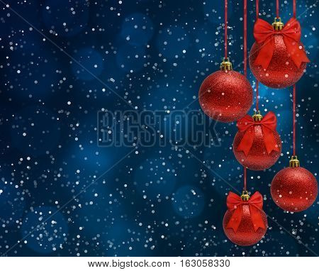 Xmas background, snow, red christmas balls hanging on ribbon bow, dark blue bokeh