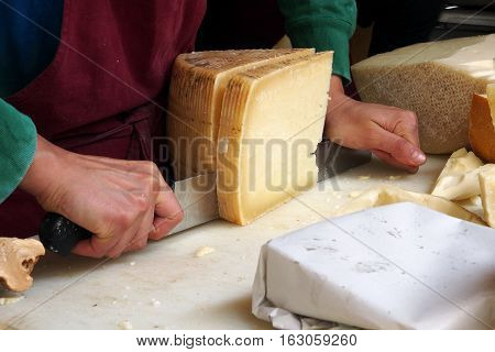 Food street market. A farmer is cutting a large slice of pecorino cheese on his stand in the street food market.