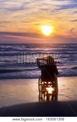 Sunset makes sightseeing on the beach a woman on a wheelchair