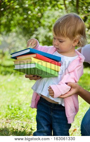 little girl holding a stack of books in color cover