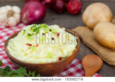 Homemade mashed potato with red and black peppers in wooden bowl. Fresh potatoes, onion, parsley and garlic on rustic table.