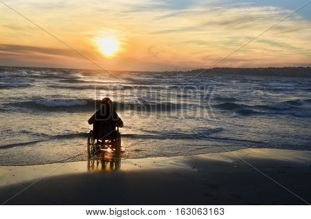 Sunset on the beach handicapped woman in wheelchair.