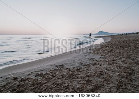 Couple embracing on the beach at sunrise