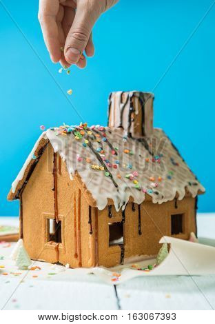 Man sprinkles Homemade gingerbread house confectionery sprinkling on blue background.