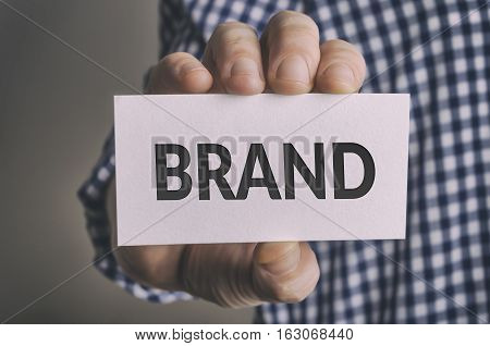 Businessman holding Brand card. Brand awareness improvement concept.
