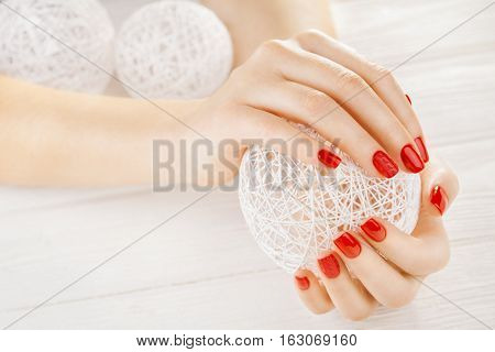 red manicure with a white ball of yarn on the white wooden table.