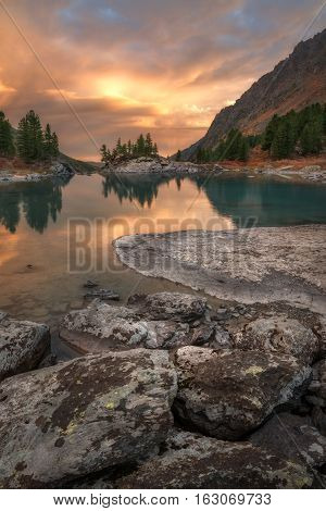 Vertical View Of Sunset Lake With A Rocky Shore, Altai Mountains Highland Nature Autumn Landscape Photo. Beautiful Russian Wilderness Scenery Image.