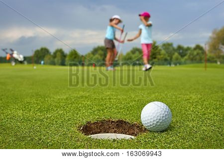 Golf ball lying on the green next to hole in the background of the two young golfers