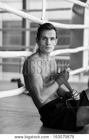 Black and white photo of young boxer in gym