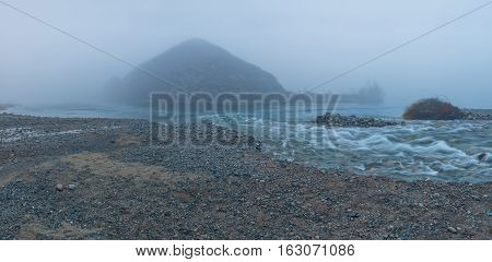Lonely Mountain In The Mist And Shallow Rive, Altai Mountains Highland Nature Autumn Landscape Photo. Beautiful Russian Wilderness Scenery Image.