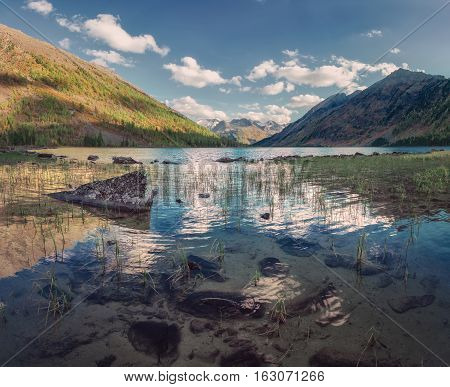 Mountain Lake With Water Reflecting Blue Sky, Altai Mountains Highland Nature Autumn Landscape Photo. Beautiful Russian Wilderness Scenery Image.