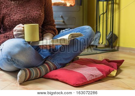 Woman is sitting down with legs crossed. She is holding a yellow tea mug and open book. Wood stove with a flickering fire are in the background.