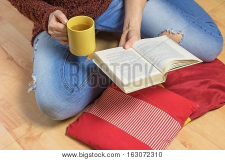 Aerial view of woman sitting down on the floor. She is holding a yellow tea mug and open book. Red pillows are lying in front of her. The letters in the book are intentionally blurred.