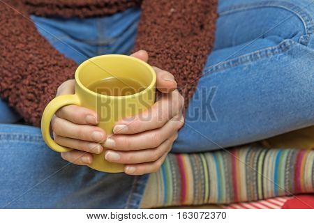 Closeup view of woman sitting down with legs crossed and holding with both hands a yellow tea mug