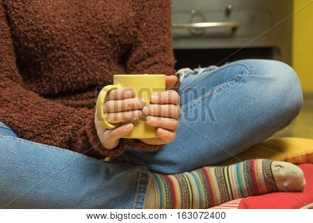 Closeup view of woman sitting down on the red pillow with legs crossed and holding with both hands a yellow tea mug. Wood stoves are in the background. Horizontally.