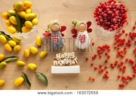 Healthy vitamin food for christmas and new year. Angels with kumquat and cranberry on wooden background.