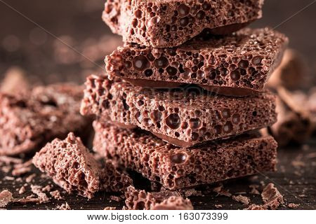 Porous Chocolate In Stack On A Wooden Background Closeup.